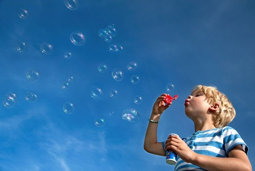 Germany, Bavaria, Boy 4_5 Years blowing soap bubbles : Stock Photo
