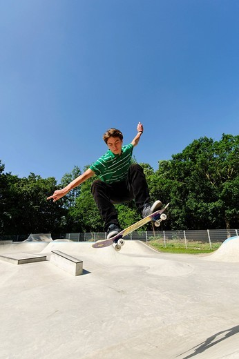 Germany, Duesseldorf, Young man performing tricks with skateboard in skatepark : Stock Photo