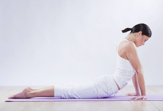 Mid adult woman doing bhujangasana against white background : Stock Photo