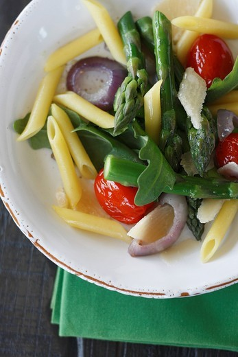 Close up of noodle salad with ruccola, asparagus, parmesan and cherry tomatoes : Stock Photo
