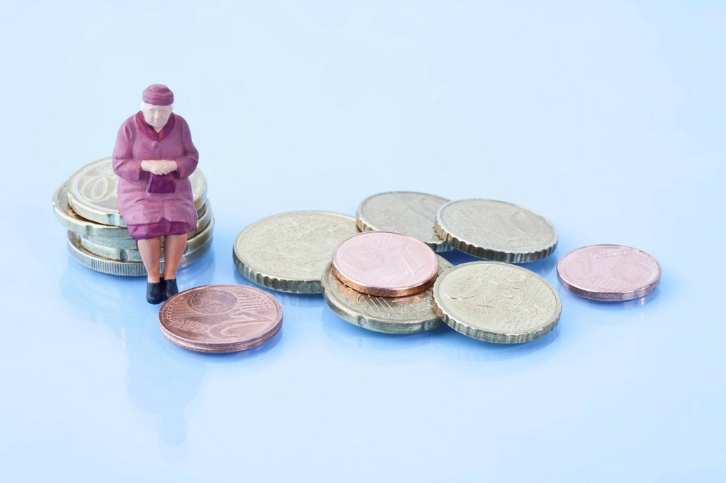Female figurine sitting on stack of euro coins : Stock Photo