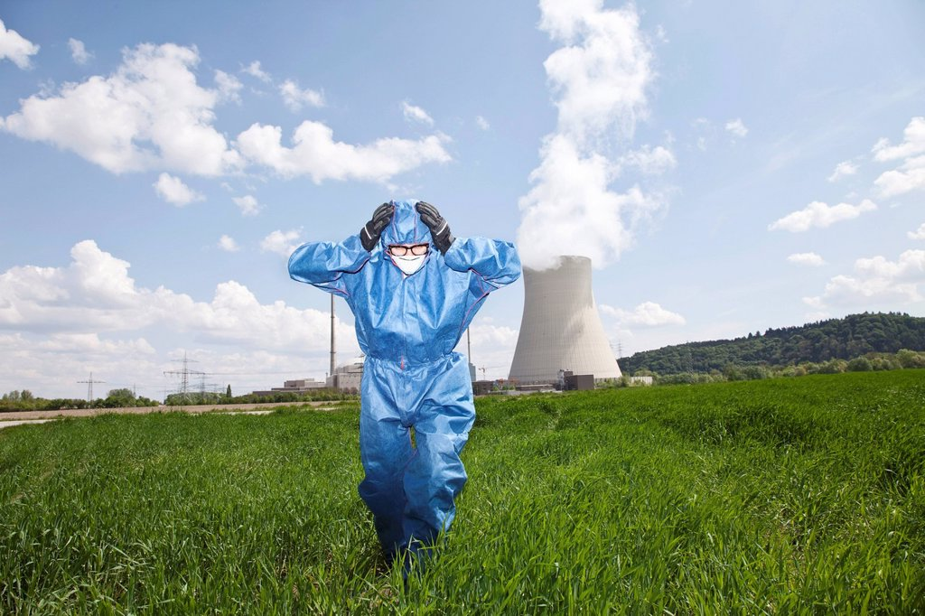Germany, Bavaria, Unterahrain, Man with protective workwear walking in field at AKW Isar : Stock Photo