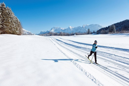 Germany, Bavaria, Isar Valley, Senior woman doing cross country skiing : Stock Photo