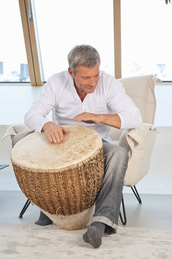Germany, Munich, Mature man playing drum at home : Stock Photo
