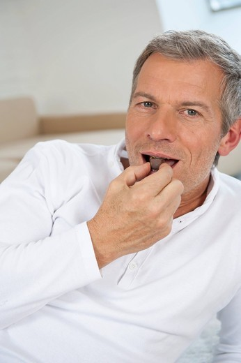 Stock Photo: 1815R-81505 Germany, Munich, Mature man eating chocolate at home, portrait