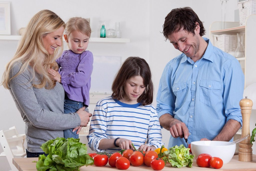 Stock Photo: 1815R-82146 Germany, Bavaria, Munich, Son preparing salad with father, mother and daughter standing besides them