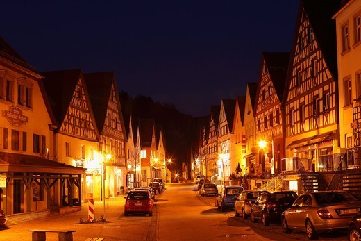 Germany, Bavaria, Franconia, Upper Franconia, Franconian Switzerland, Pottenstein, View of town with timber framed houses at night : Stock Photo
