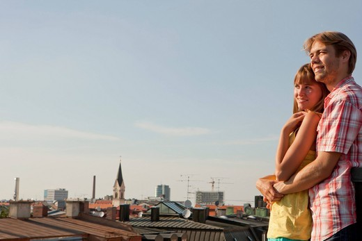 Germany, Bavaria, Munich, Young couple enjoying on rooftop with city in background : Stock Photo