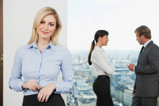 Germany, Frankfurt, Business woman smiling with business people talking in background : Stock Photo