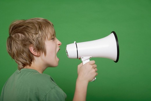 Stock Photo: 1815R-84386 Close up of boy screaming in megaphone against green background
