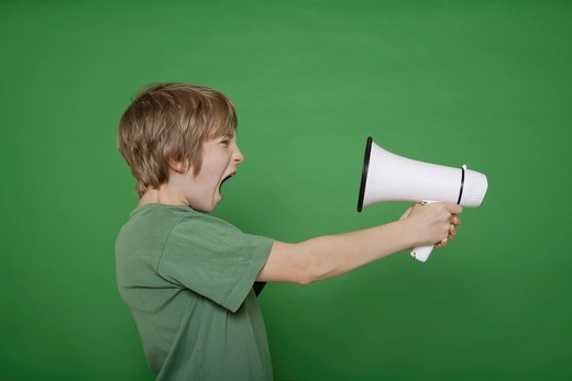 Boy screaming in megaphone against green background : Stock Photo