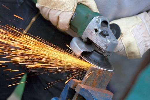 Close up of man sharpening piece of iron with angle grinder : Stock Photo