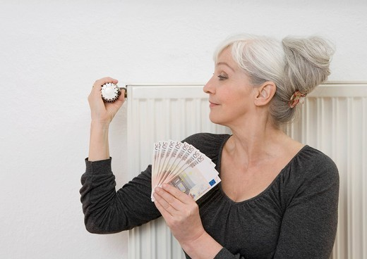 Stock Photo: 1815R-84957 Germany, Duesseldorf, Woman holding banknotes and adjusting heater at home