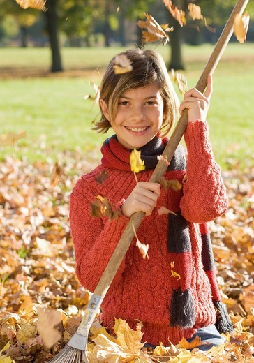 Germany, Nuremberg, Girl with rake in leaves, smiling, portrait : Stock Photo