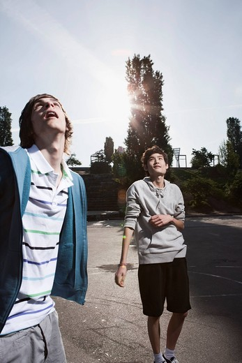 Germany, Berlin, Teenage boys standing in playground, looking up : Stock Photo