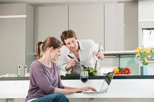 Germany, Hamburg, Man preparing salad with woman using laptop in kitchen : Stock Photo