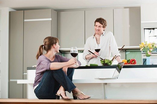 Germany, Hamburg, Man and woman in kitchen, smiling : Stock Photo