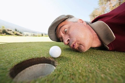 Italy, Kastelruth, Mature man blowing golf ball into hole : Stock Photo