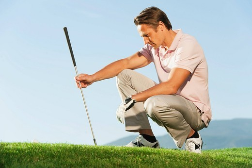 Italy, Kastelruth, Mid adult man with golf club on golf course : Stock Photo