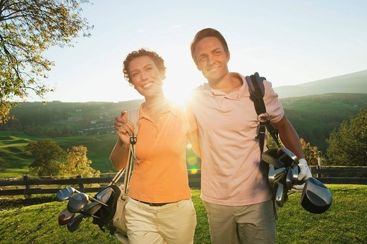 Stock Photo: 1815R-87529 Italy, Kastelruth, Golfers with golf bag walking and smiling