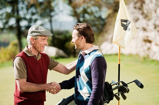 Italy, Kastelruth, Golfers shaking hands on golf course, smiling : Stock Photo