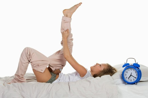 Girl lying on bed getting dressed : Stock Photo