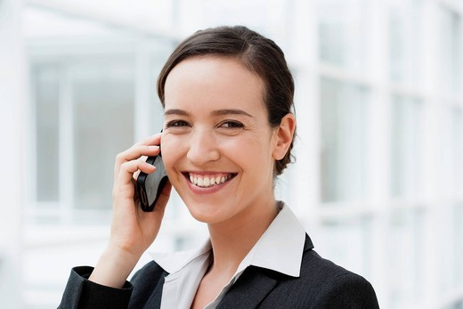 Stock Photo: 1815R-89806 Germany, Bavaria, Diessen am Ammersee, Young businesswoman talking on mobile phone, smiling, portrait