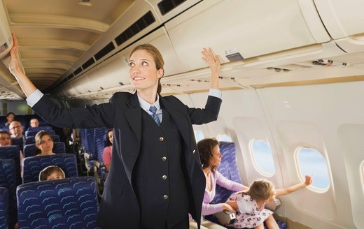 Germany, Munich, Bavaria, Stewardess checking lockers in economy class airliner : Stock Photo