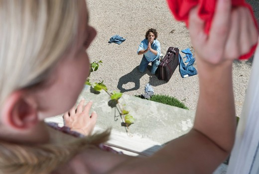 Italy, Tuscany, View of guilty young man with luggage from hotel window : Stock Photo