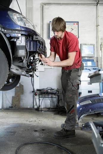 Germany, Ebenhausen, Mechatronic technician working in car garage : Stock Photo