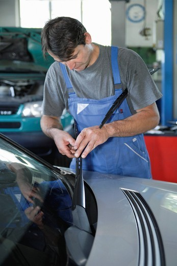 Germany, Ebenhausen, Mechatronic technician working in car garage : Stock Photo