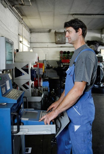 Germany, Ebenhausen, Mechatronic technician working on computer in car garage, close up : Stock Photo