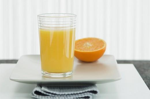 Stock Photo: 1815R-91149 Glass of orange juice with half orange in plate