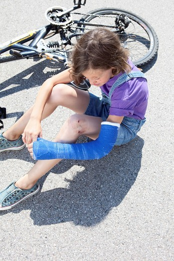 Stock Photo: 1815R-91414 Germany, Bavaria, Wounded girl sitting on road after bicycle accident