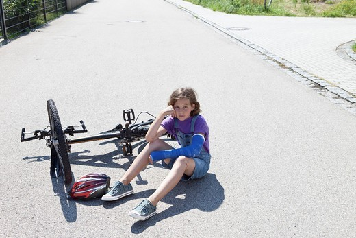 Germany, Bavaria, Wounded girl sitting on road after bicycle accident : Stock Photo