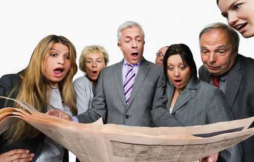 Business people shocked while reading newspaper against white background : Stock Photo