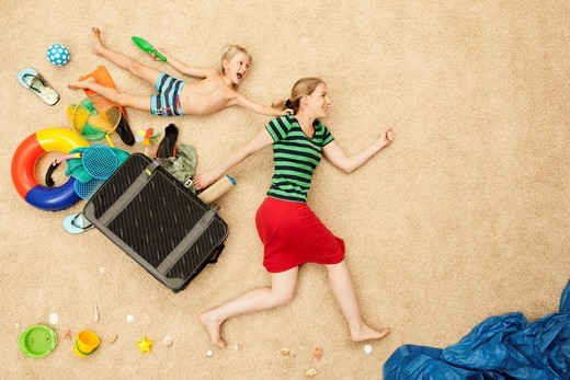 Germany, Mother and son with toys and baggage at beach : Stock Photo