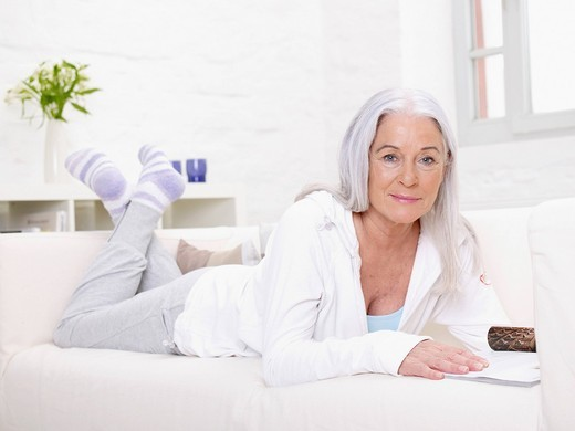 Stock Photo: 1815R-92375 Germany, Hamburg, Senior woman lying on sofa with magazine, portrait