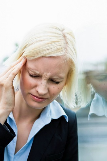 Germany, Bavaria, Munich, Young woman suffering from headache : Stock Photo