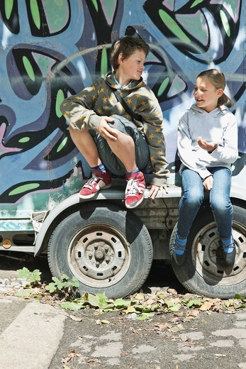 Germany, Berlin, Boy and girl sitting on graffiti truck : Stock Photo