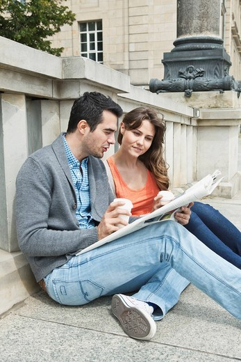 Germany, Berlin, Couple sitting on sidewalk and reading newspaper : Stock Photo