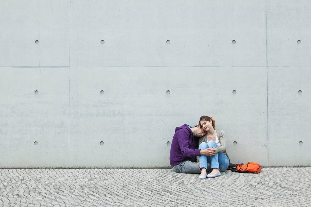 Stock Photo: 1815R-93457 Germany, Berlin, Couple sitting in front of large wall on sidewalk