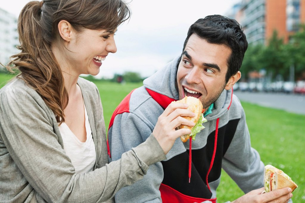 Germany, Berlin, Couple eating food in park : Stock Photo