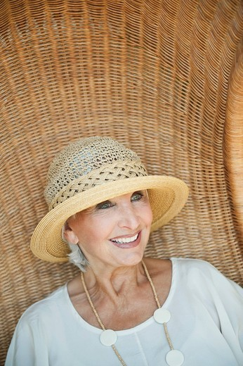 Stock Photo: 1815R-93500 Germany, Bavaria, Senior woman sitting on wicker chair, smiling