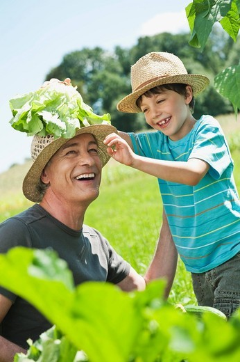 Stock Photo: 1815R-93596 Germany, Bavaria, Grandfather with grandson in vegetable garden, smiling