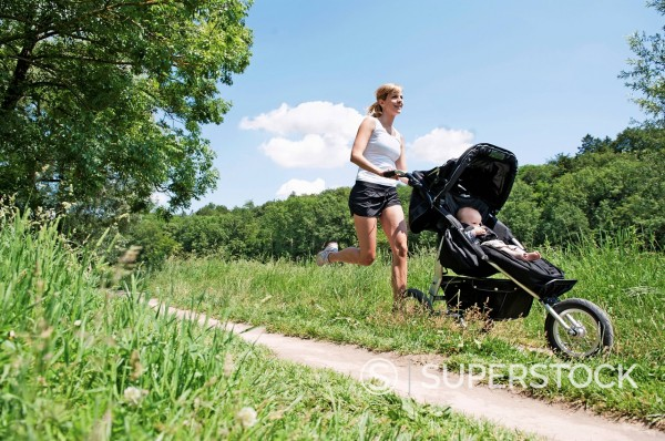 Stock Photo: 1815R-93734 Germany, Munich, Mother jogging with baby boy in pram, smiling