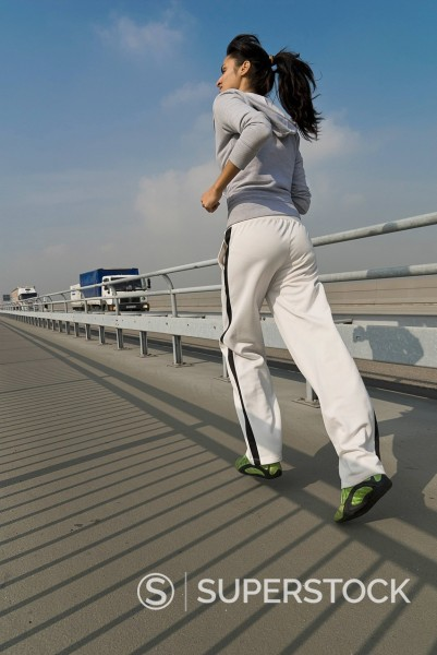 Stock Photo: 1815R-93820 Germany, North Rhine_Westphalia, Duesseldorf, Young woman running on bridge