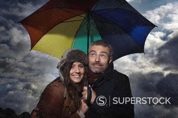 Germany, Cologne, Couple with umbrella, smiling : Stock Photo