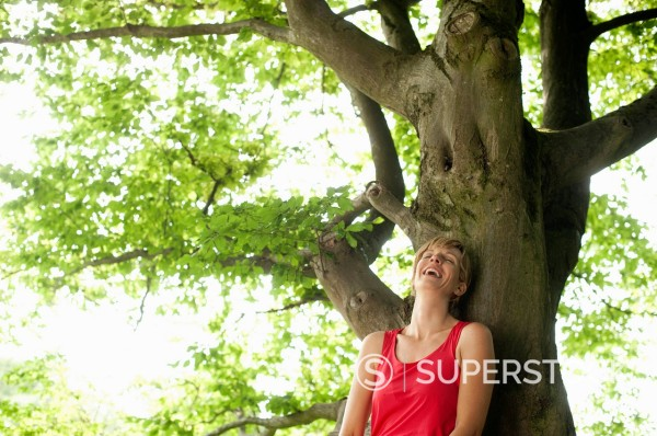 Germany, Bavaria, Mid adult woman leaning on tree, smiling : Stock Photo
