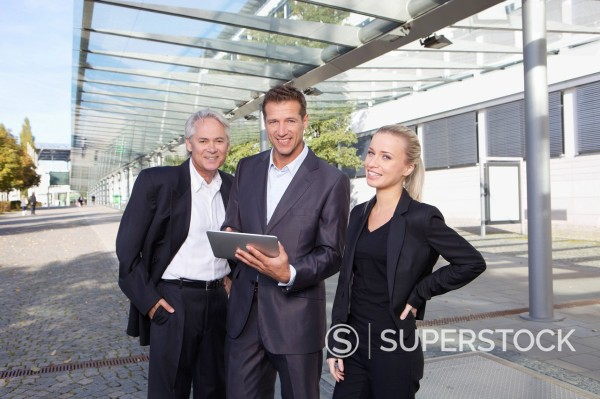 Stock Photo: 1815R-94256 Germany, Bavaria, Munich, Business people using digital tablet, smiling, portrait